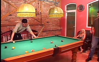 blond plays with dong stiicks on pool table
